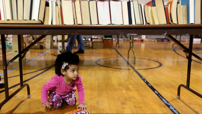 Zuri Mwepu, 2, of Salem, crawls under tables of books during the 63rd annual YMCA Used Book Sale in Salem on Saturday, March 4, 2017. The sale continues Sunday with readers able to buy all they books they can fit into a bag for $3 and a box for $5.