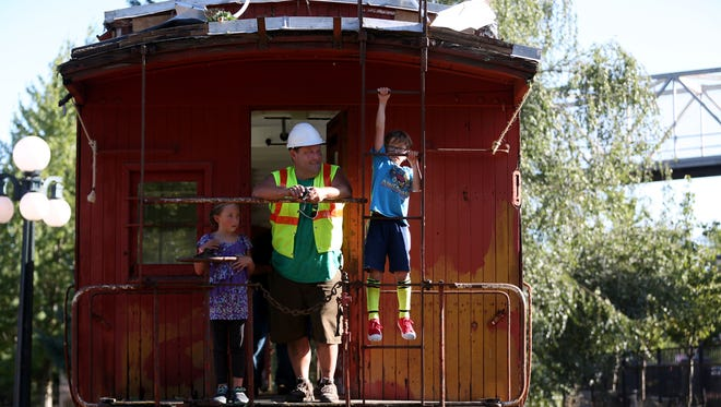 Sean O'Harra, the operations director of the Willamette Heritage Center, checks out Caboose #507, built in 1913, with his children, Maddy O'Harra, 8, and Hunter O'Harra, 7, outside the Willamette Heritage Center in Salem on Friday, July 28, 2017.