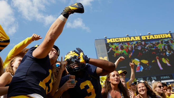 Wolverines defensive ends Chase Winovich and Rashan Gary snap a selfie with the Michigan student section after defeating Cincinnati at Michigan Stadium on Sept. 9, 2017.