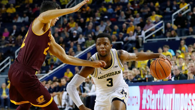 Michigan guard Zavier Simpson (3) dribbles defended by Central Michigan guard Matt Beachler (22) in the first half on Monday, Nov. 13, 2017, at Crisler Center.