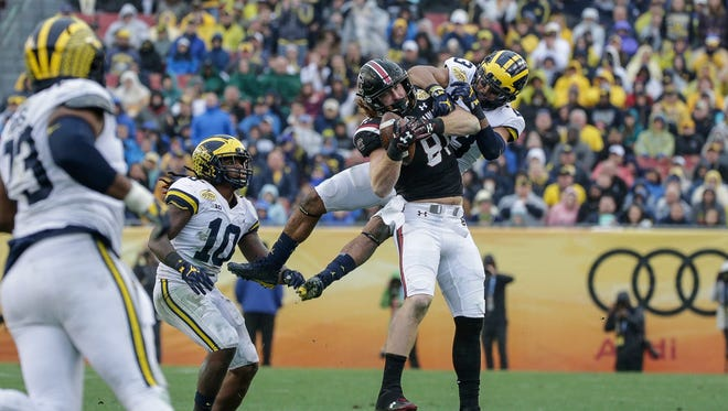 Michigan Wolverines defensive back Tyree Kinnel tackles South Carolina tight end Hayden Hurst in the second half of the Outback Bowl at Raymond James Stadium in Tampa, Fla., Monday, Jan. 1, 2018.