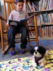 Sammy Maaraba, 6, of Pittsford reads to Annie at the Brighton library.