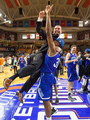 UNC Asheville's Sam Hughes (31) lifts coach Nick McDevitt into the air after winning an NCAA college basketball championship game in the Big South Conference tournament in Buies Creek, N.C., Sunday, March 6, 2016. (AP Photo/Ben McKeown)