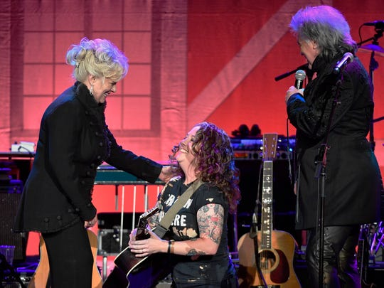 Ashley McBryde, center bows down before Country Music
