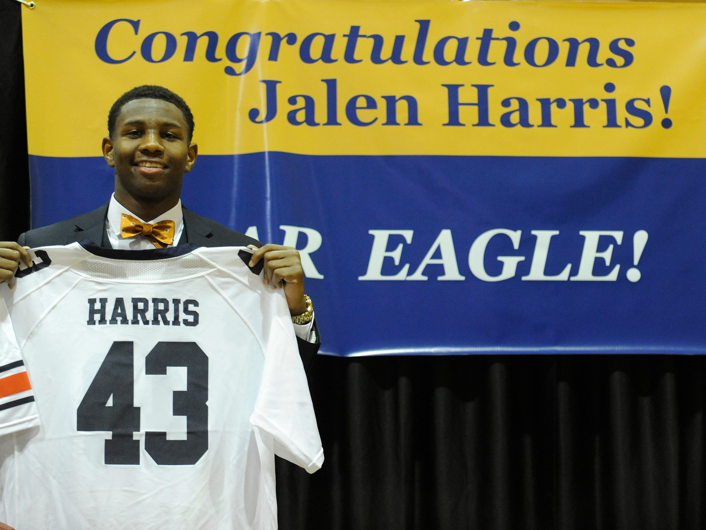 St. James High School's Jalen Harris holds up an Auburn Jersey with his name on it as he announces that he is signing to play college football at Auburn on Wednesday February 4, 2015 at St. James in Montgomery, Ala.