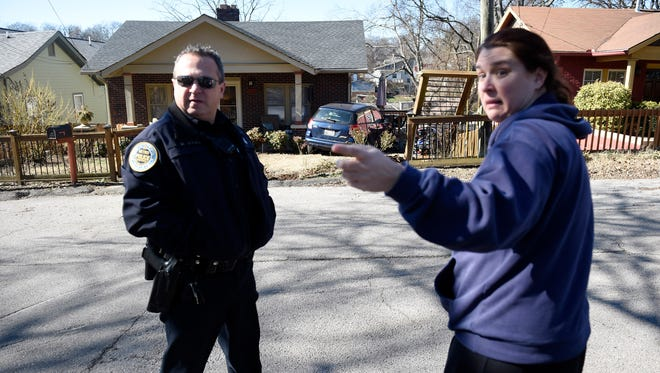 Officer David Boone questions Colleen Pisruzny about the neighbor's car that rolled down the hill and landed in her front yard, Monday, Jan. 30, 2017 in Nashville, Tenn.
