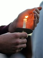 A candle burns during a Pi Kappa Alpha and Faith House candlelight vigil against domestic violence Thursday night in the UL quad.