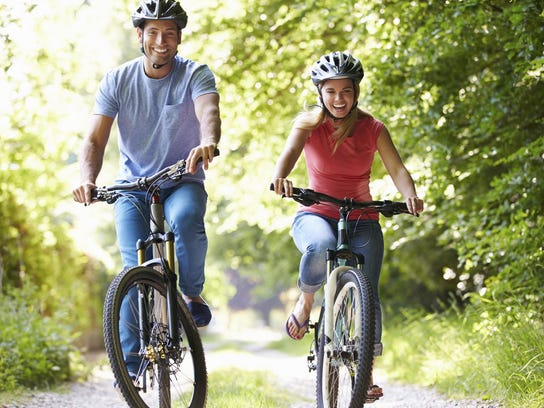 A man and woman are biking.