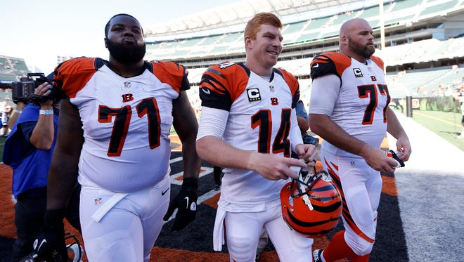 Bengals quarterback Andy Dalton (14) walks off the field with tackles Andre Smith (71) and Andrew Whitworth after a win against the Falcons at Paul Brown Stadium in September of 2014.