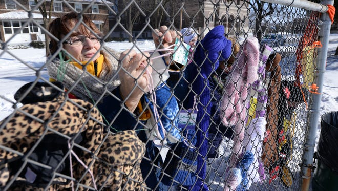 Cynthia Olsen of Lifting Up Green Bay, left, along with Julie Rathe, hangs scarves, gloves and hats on a fence Saturday near the St. John the Evangelist Homeless Shelter.
