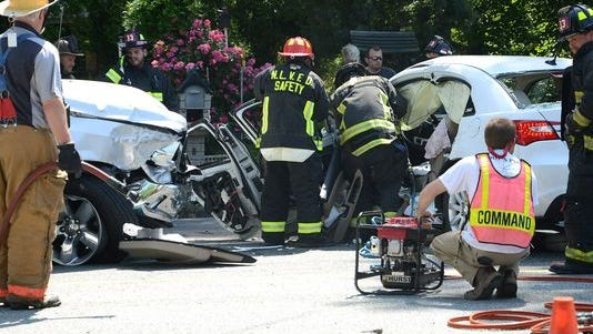 North Lenoir firefighters remove the driver side door after a woman, pinned in her white vehicle, was rescued using the jaws of life on U.S. 258 North on May 13, 2014, in Kinston, N.C.