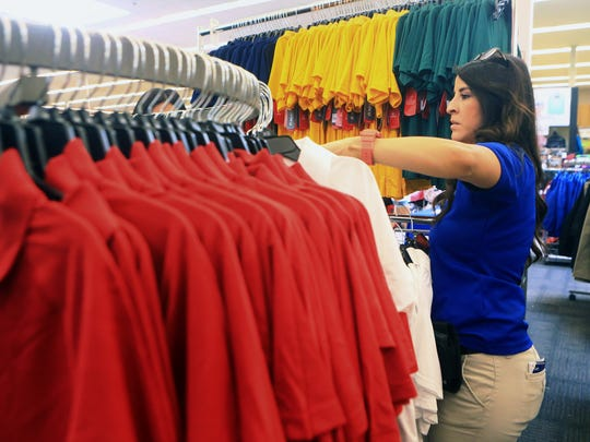 Team Leader Amy Ramirez from Academy Sports + Outdoors adds shirts on a rack as the store prepares for Tax Free Weekend on Thursday, Aug. 10, 2017, in Corpus Christi.