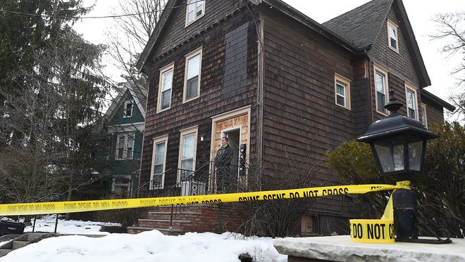 Law enforcement officials investigate a crime scene at 23 Oak Street in Binghamton on Friday, March 9, 2018.