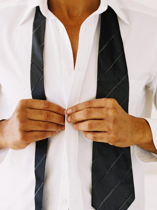 close-up of a man's hands buttoning a shirt