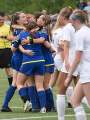 Marian players congratulate Ellie DeConinck after scoring
