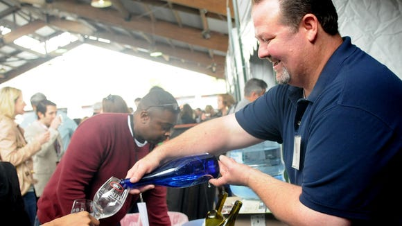 Adam Bullock pours wine for people during the 2014 CORK wine festival for the Red River Revel at Festival Plaza in downtown Shreveport.