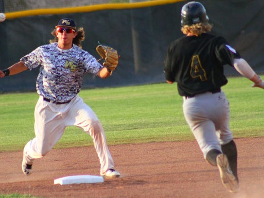 Aaron Olivas, left, receives a throw from the catcher