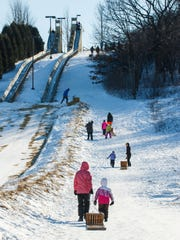 Toboggan enthusiasts trek up the hill for another ride at Lowell Park in Waukesha during the 2016 Waukesha JanBoree.