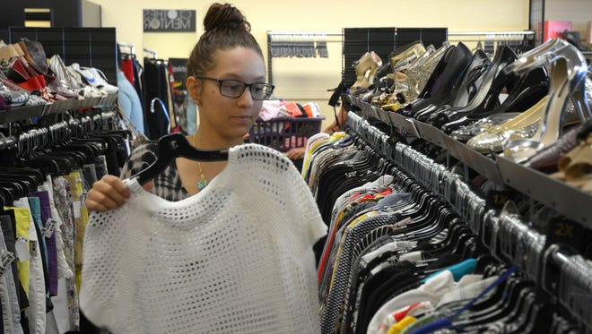 Dairyon Lewis puts a dress on the rack at the Clothes Mentor at Rural and Ray roads in Chandler.