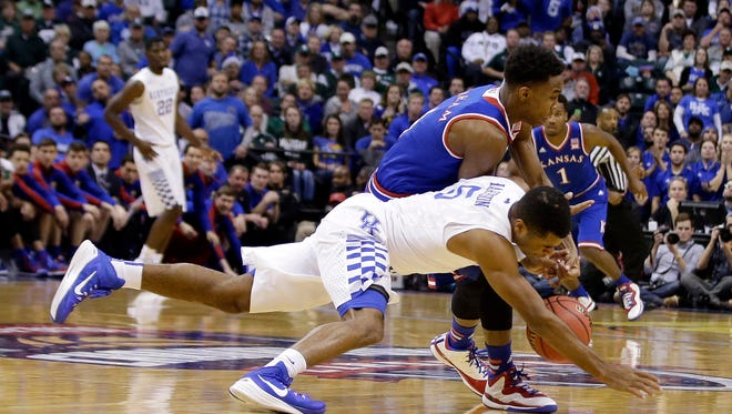 Kentucky's Andrew Harrison (5) and Kansas's Devonte Graham (4) battle for a loose ball during the first half of an NCAA college basketball game Tuesday, Nov. 18, 2014, in Indianapolis. (AP Photo/Darron Cummings)