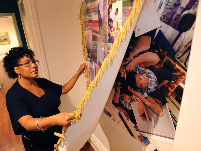 """Dover artist Lori Crawford installs her """"Sista's"""" exhibit at the Biggs museum."""