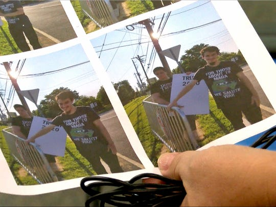 A woman holds a photo that shows Morris May in Bedmininster in the area set up for protestors when President Donald Trump was staying at his golf course nearby.  He is wearing the same shirt that he wore on the day he assaulted Allison Kolarik.