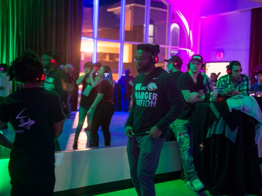 Attendees dance at a silent disco party Saturday, Jan.