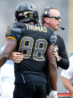 Southern Miss wide receiver Michael Thomas (88) is congratulated by head coach Todd Monken after scoring a touchdown in the first quarter against the Washington Huskiesat Cotton Bowl Stadium.