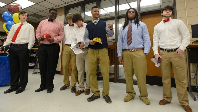 Prattville High School football players on signing day, from left, Austin Aaron who is going to Bringham Southern, Kenny Thomas, who is going to Louisville, Seth Knotts who is going to West Alabama, Donavan Boone who is going to Huntingdon, Kenny Thomas who is going to Michigan, Ricky Franklin who is going to Hutchinson Community College and Kegan Smith who's is going to West Alabama at the school in Prattville, Ala. on Wednesday February 4, 2015.