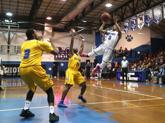 Godby's Tavaris King shoots a fall away shot over Rickards' Tyrin Card during their game at Godby High School on Friday, Jan. 5, 2018.