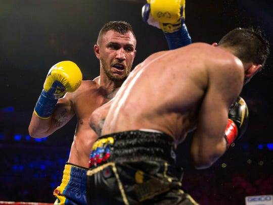 Vasiliy Lomachenko, left, punishes, Jorge Linares.