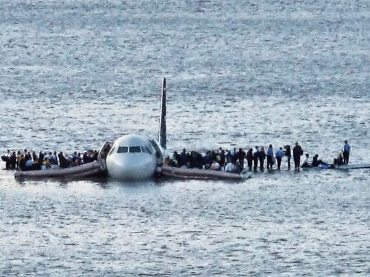In this Thursday Jan. 15, 2009 file photo, airline passengers wait to be rescued on the wings of a US Airways Airbus 320 jetliner that safely ditched in the frigid waters of the Hudson River in New York, after a flock of birds knocked out both its engines.