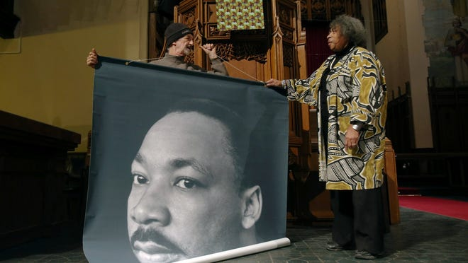 Dorothy Aldridge and Ken Parks of Detroit set up a display honoring Martin Luther King at Central United Methodist Church in Detroit on Saturday, January 17, 2015.