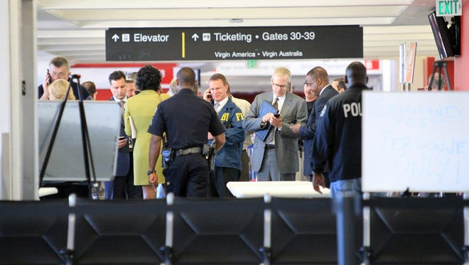 Federal and local investigators gather in Terminal 3 at Los Angeles International Airport where a gunman armed with a semi-automatic rifle opened fire, killing a Transportation Security Administration employee and wounding two other people.