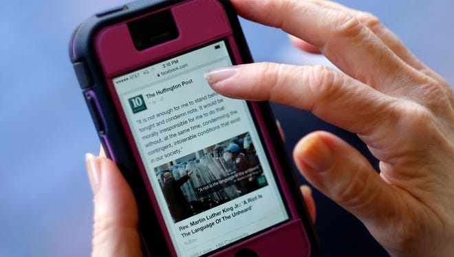 In this Tuesday, April 28, 2015 photo, an unidentified person uses a mobile phone to read the news from The Huffington Post on Facebook, in Los Angeles. ìState of the News Media 2015,î published Wednesday, April 29, 2015, by the Pew Research Centerís Journalism Project found that nearly half of Web users learn about politics and government from Facebook, roughly the same percentage as those who seek the news through local television and double those who visit Yahoo or Google News.
