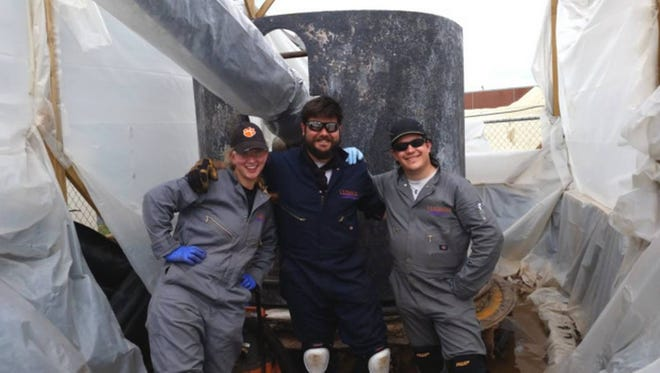Clemson University's conservation team poses with the USS Maine gun before it was restored. Pictured, from left are historic preservation specialists Claire Achtyl and Justin Schwebler along with assistant conservator Christopher McKenzie.