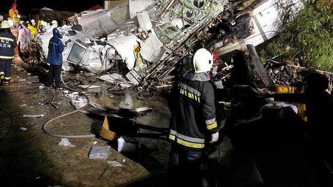Rescue workers survey the wreckage of TransAsia Airways Flight GE222, which crashed while attempting to land in stormy weather on the Taiwanese island of Penghu on July 23.