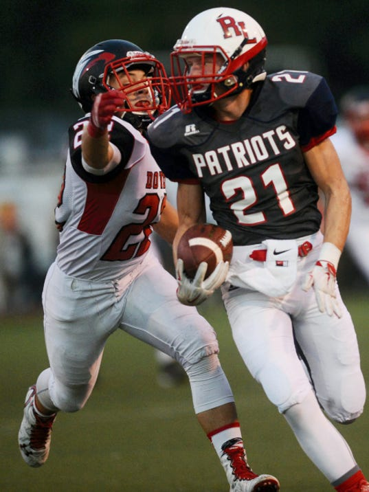 Dover's Caden Snyder reaches for Red Land's Kyle Campbell as Campbell makes a run during Friday's game at West Shore Stadium in New Cumberland. The Patriots won, 38-21.