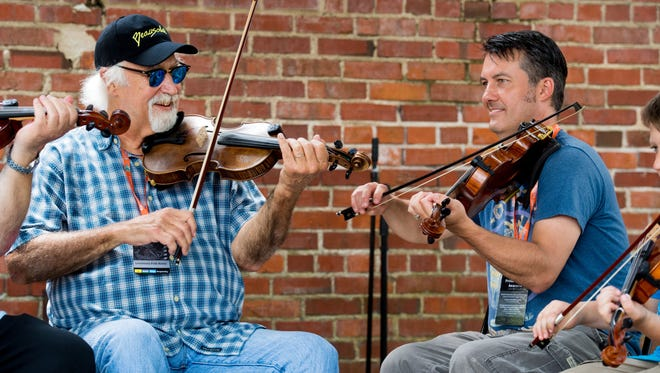 Mitch Reed, right, sits jams with BeauSoleil leader Michael Doucet last April at a Louisiana Folk Roots jam session in downtown Lafayette.