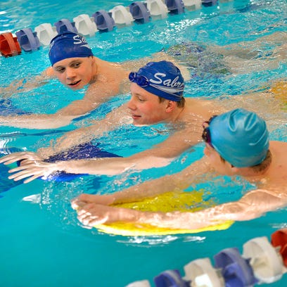 Sartell swimmers (from left) Mitchell Dockendorf, Spencer Sathre and Jake Martin talk as they warm up at the beginning of practice Tuesday at Sartell High School. The team is sending 10 swimmers to state.