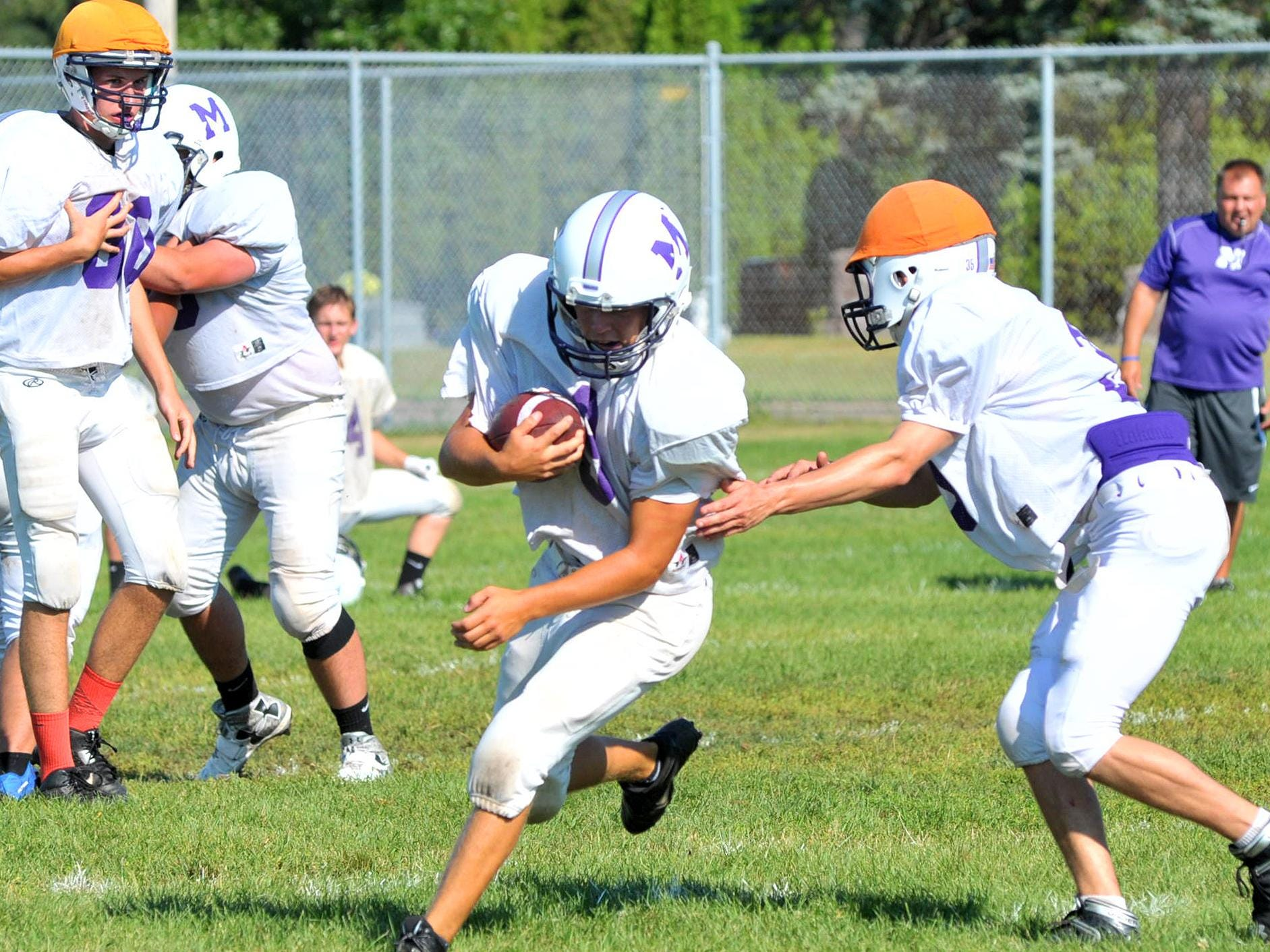 Mosinee's Landon Stepan(9), middle, avoids being tagged while running the ball during Monday's practice at Mosinee High School football field.