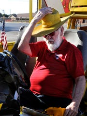 """Sitting behind the wheel of his """"Trump Mobile"""", Bob Terry puts on the yellow-painted straw hat he keeps in it. """"Bob Terry Yellow"""" originated as a way for his crop dusting planes to be easily recognizable from the air. Years later, it's his signature color around Roby. The Trump Mobile is parked at the intersection of U.S. 180 and State Highway 70."""