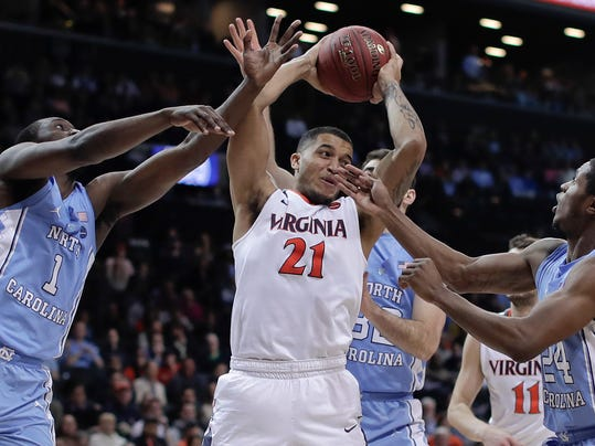 Virginia forward Isaiah Wilkins (21) pulls down a rebound between North Carolina forward Theo Pinson (1), guard Kenny Williams (24) and forward Luke Maye (32) during the second half of an NCAA college basketball game for the Atlantic Coast Conference men's tournament title Saturday, March 10, 2018, in New York. Virginia won 71-63. (AP Photo/Julie Jacobson)