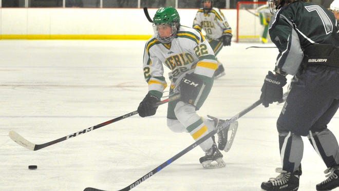 Pueblo County's Ryan Nicoll, center, looks to pass past the defense of Pine Creek's Austin Gipson during the Hornets' 6-2 loss to Pine Creek on Jan. 19, 2019 at the Pueblo Ice Arena.