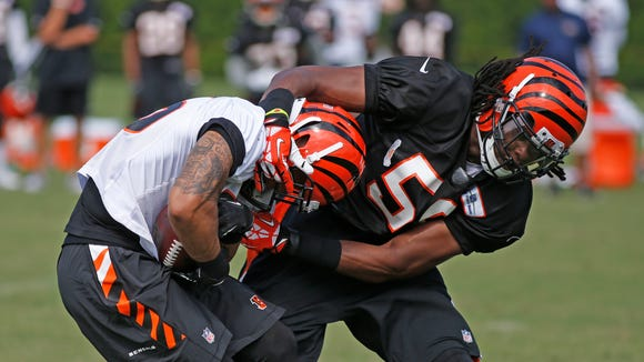 Cincinnati Bengals wide receiver Colin Lockett (15) catches a pass despite the defensive efforts of Vontaze Burfict during the Bengals training camp held at Paul Brown Stadium Friday.