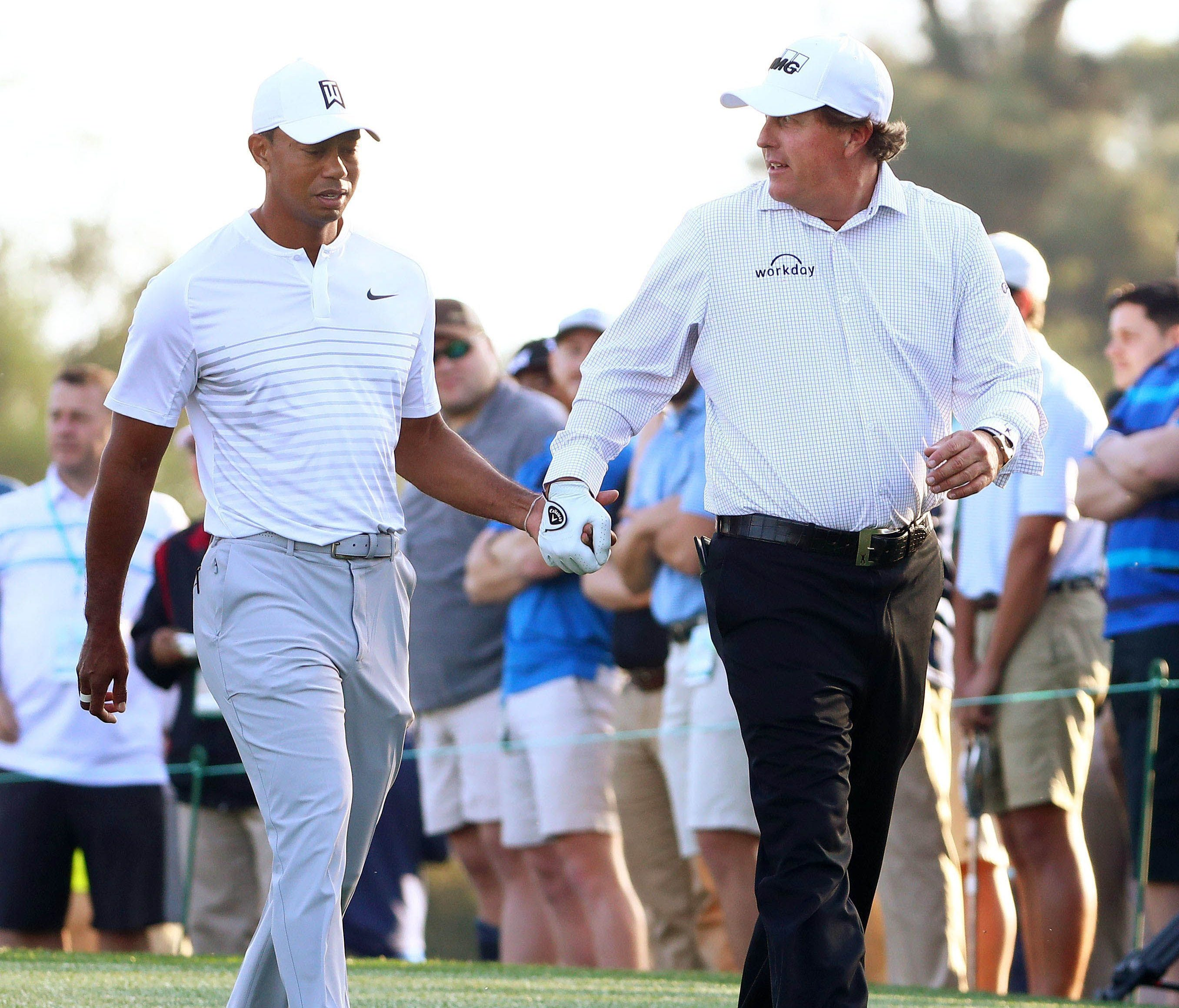 Tiger Woods and Phil Mickelson walk off the 10th tee box hand-in-hand during a practice round for the Masters Tournament at Augusta National Golf Club in Augusta, Ga.