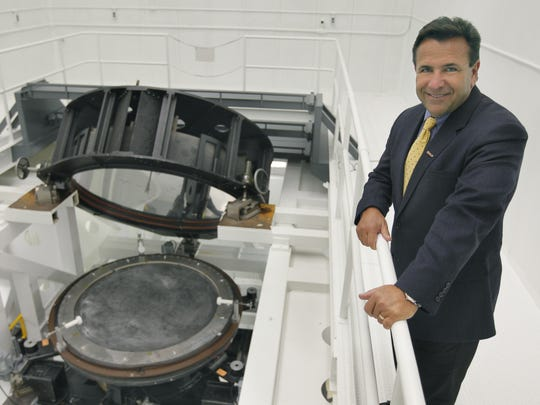 Vice president of operations Michael Ognenovski of Exelis Geospatial Systems, next to the reference sphere for optical testing at the large optical test tower in Rochester, N.Y. on Thursday March 20 2014. The company makes optics that are used in drones, satellites and GPS systems.