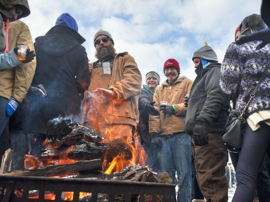 People gather at a fire pit at the Winter Beer Festival at Fifth Third Ballpark in Comstock Park, Mich. on Friday, Feb. 27, 2015.