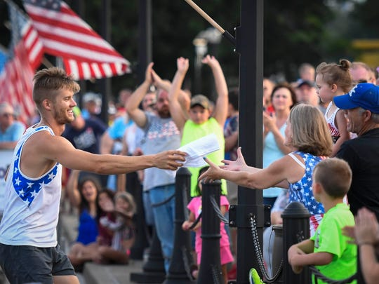 "Former Indiana University and University of North Carolina pole vaulter Scott Houston hands out t-shirts after clearing 18'-2""1/2 to win the 11th annual Jammin' & Jumpin' Street Vault event at the Henderson riverfront Tuesday, July 4, 2017."
