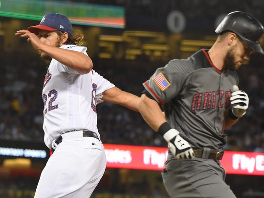Chris Owings breaks up a no-hitter as he beats the tag by Clayton Kershaw in the seventh inning on Tuesday.
